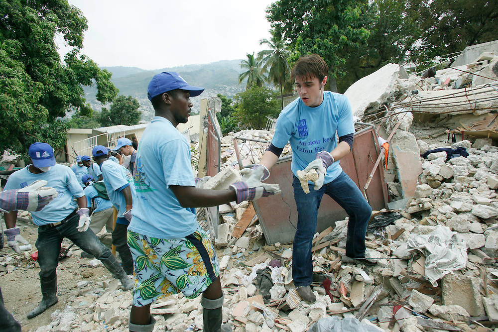 American Idol winner Kris Allen hands rubble to a Haitian man while working in a United Nations program to clear the remains of homes flattened by the devastating Jan 12th earthquake in Port-au-Prince, Haiti, Friday, Feb. 19, 2010. (Stuart Ramson for United Nations Foundation)