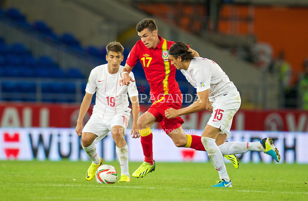 CARDIFF, WALES - Tuesday, September 10, 2013: Wales' Gareth Bale in action against Serbia's Dejan Lekic during the 2014 FIFA World Cup Brazil Qualifying Group A match at the Cardiff CIty Stadium. (Pic by David Rawcliffe/Propaganda)