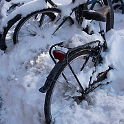 Winter urban New York City snow street scene with bikes covered with snow