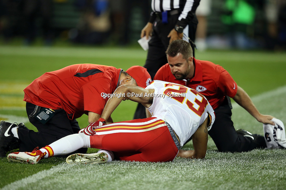 Kansas City Chiefs cornerback Phillip Gaines (23) gets medical attention from the Chiefs staff as he lies on the end zone grass holding his knee during the 2015 NFL week 3 regular season football game against the Green Bay Packers on Monday, Sept. 28, 2015 in Green Bay, Wis. The Packers won the game 38-28. (©Paul Anthony Spinelli)