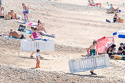 © Licensed to London News Pictures. 07/08/2020. Brighton, UK. Members of the public take advantage of the early morning sunshine to sunbath on the beach in Brighton and Hove as temperatures are expected to be the hottest of the year so far. Photo credit: Hugo Michiels/LNP