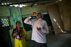 Mohammad Haroon Khan takes his daily medicine while Hanifa Hussain Sayed, a community health worker with a local NGO, watches at the Padel Nagar DOTS center.