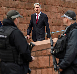 © Licensed to London News Pictures. 03/10/2017. Manchester, UK. Chancellor PHILIP HAMMOND walks past armed police officers on day three of the Conservative Party Conference. The four day event is expected to focus heavily on Brexit, with the British prime minister hoping to dampen rumours of a leadership challenge. Photo credit: Ben Cawthra/LNP