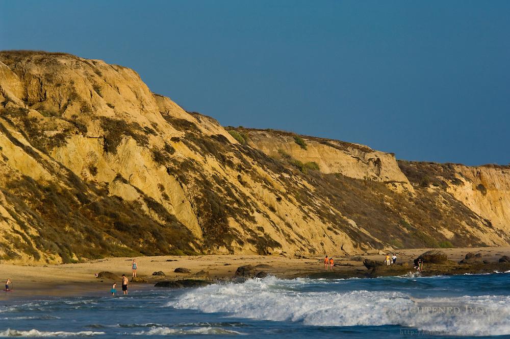 People walking on sand beach below cliffs at Crystal Cove State Park, Corona del Mar, Newport Beach, Orange County, California