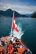 The Swiss flag drapes off the back of a paddlewheel steamboat cruise on Lake Lucerne, Switzerland.