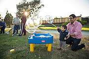 Aneesh Bendre helps his son Rinu, 1, make bubbles during National Night Out at Sandalwood Park in Milpitas, California, on August 4, 2016. (Stan Olszewski/SOSKIphoto)