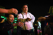 "Jeans factory bosses raise to the toast: ""To the millionaires of Zhongshan"" in Zhongshan city, China. .This picture is part of a photo and text story on blue jeans production in China by Justin Jin. .China, the ""factory of the world"", is now also the major producer for blue jeans. To meet production demand, thousands of workers sweat through the night scrubbing, spraying and tearing trousers to create their rugged look. .At dawn, workers bundle the garment off to another factory for packaging and shipping around the world..The workers are among the 200 million migrant labourers criss-crossing China.looking for a better life, at the same time building their country into a.mighty industrial power."