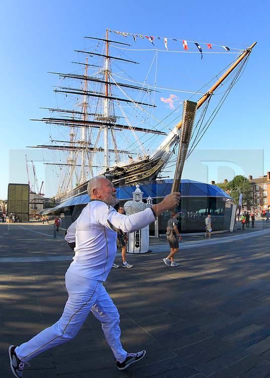 © Licensed to London News Pictures. 21/07/2012, London, UK.  Sir Robin Knox-Johnson, the first person to sail single handed non-stop around the world, carries the London 2012 Olympic Torch around the Cutty Sark, a 1869 tea clipper, in Greenwich, London during the Olympic Torch Relay, Saturday, July 21, 2012. Photo credit : Sang Tan/LNP