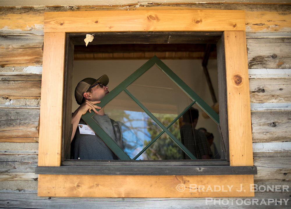 Kevin Brothers looks for a reference number on a window in one of the cabins at the White Grass Ranch. Part of the restoration and preservation process involves labling pieces of historical structures to keep track of their proper place.