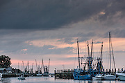 Shrimp boats docked along Shem Creek at sunset in Mount Pleasant, South Carolina.