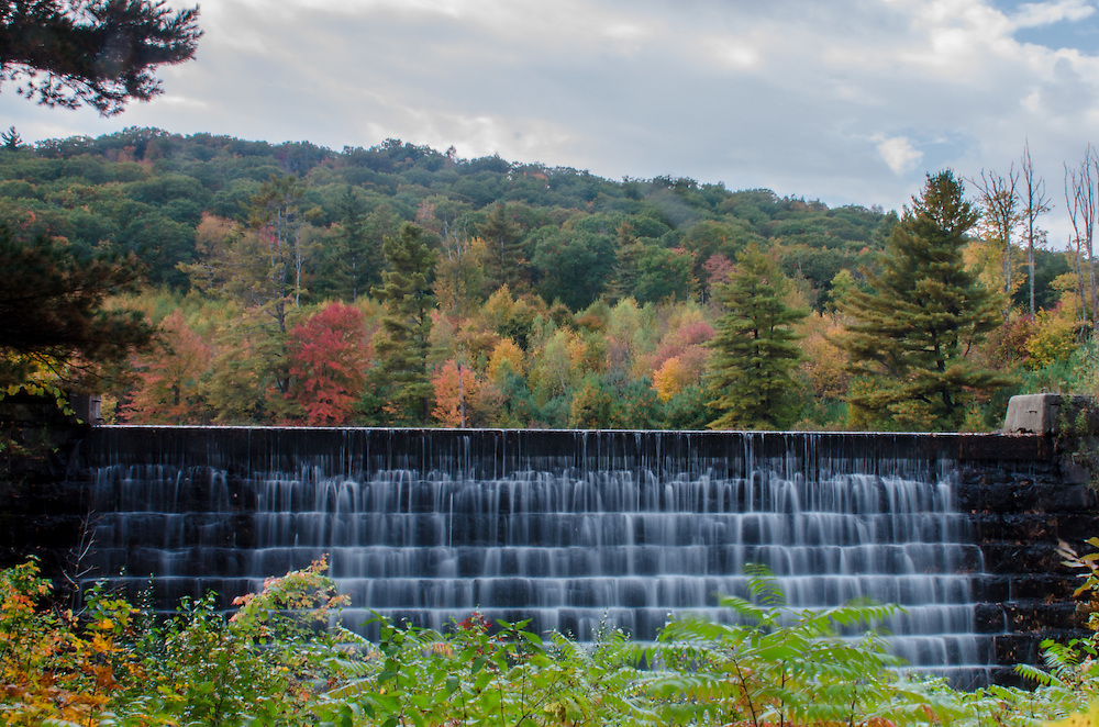 Fall Foliage as water spills out of the Rugg Brook Reservoir.