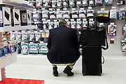 A passenger stoops to inspect travel adapters and plugs at Dixons Digital in Heathrow airport's terminal 5