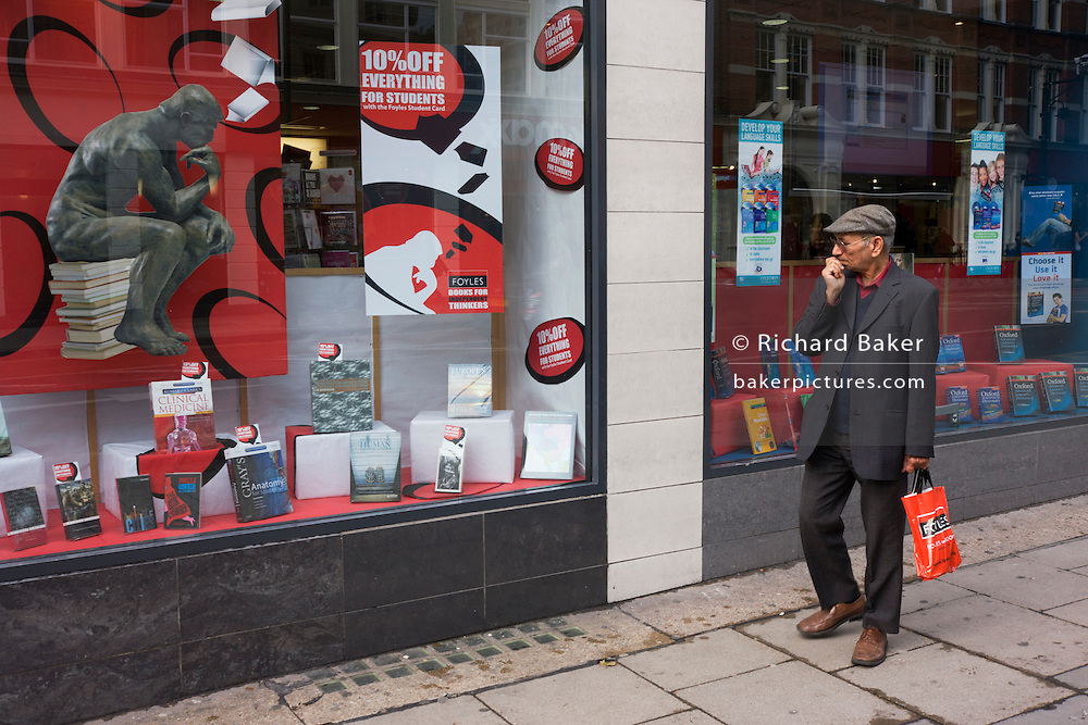Near Rodin's Thinker poster, a Foyles bookshop customer window shops outside the shop in London, Charing Cross Road.