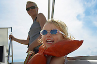 Girl (5-6) with mother on yacht focus on foreground