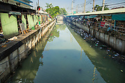 "26 SEPTEMBER 2012 - BANGKOK, THAILAND: Khlong Toey runs along Khlong Toey Market in Bangkok. Khlong is the Thai word for canal. This canal used to go all the way to the old imperial center of Bangkok but has been filled in now. This stretch of the canal is used for waste water from the market. Khlong Toey (also called Khlong Toei) Market is one of the largest ""wet markets"" in Thailand. The market is located in the midst of one of Bangkok's largest slum areas and close to the city's original deep water port. Thousands of people live in the neighboring slum area. Thousands more shop in the sprawling market for fresh fruits and vegetables as well meat, fish and poultry.     PHOTO BY JACK KURTZ"