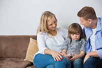Parents sitting with upset son on sofa at home