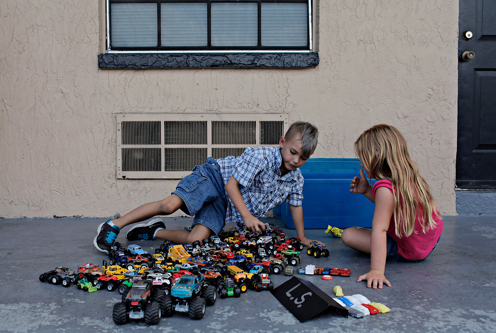 MELISSA LYTTLE | Times<br /> Leland Steffan, 7, plays with his monster truck collection outside of the motel room he lives in, along with a friend and neighbor, Laila Roegele, 6, who lives a few doors down from him at the Mosley Motel.