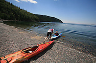 Man pushes wife in kayak out onto Lake Superior from stony beach at Terrace Bay, Ontario; Canada.