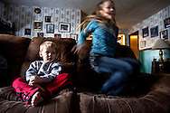 Ju Ju jumps on the couch while her brother Titus watches a movie. The two siblings are the youngest of the Deeds children, and were both  born after their parents began fostering children.