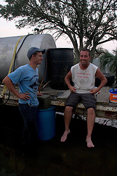 25 Sept, 2005.  Carlyss, Louisiana. Hurricane Rita aftermath. <br /> L/R Local man Aaron Stokes helps neighbour Harold Herman to syphon diesel fuel from a 500 gallon drum for use in Harold's generator. Locals helped each other through the aftermath of the storm. Harold wears a T-shirt that reads 'Laissez les Bon Temps Rouler' which translates to 'let the good times roll.'<br /> Photo; &copy;Charlie Varley/varleypix.com