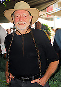 NEW YORK - JUNE 11: Farm Aid President Willie Nelson poses at a stall in the Farmer's Market before the press conference announcing plans for Farm Aid in Union Square Park on June 11, 2007 in New York City.