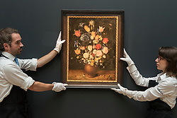 "© Licensed to London News Pictures. 01/07/2016. London, UK.  Technicians prepare to hang ""Still Life of flowers in a stoneware vase"" by Jan Breughel The Elder (est. GBP 3-5 million), at the preview of Sotheby's London Old Masters evening sale which takes place 6 July.   Photo credit : Stephen Chung/LNP"
