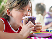 Girl (10-12) eating cupcake at birthday party