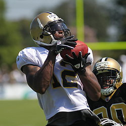 July 31, 2011; Metairie, LA, USA; New Orleans Saints wide receiver Marques Colston (12) catches a pass over rookie safety Isa Abdul-Quddus (20) during training camp practice at the New Orleans Saints practice facility. Mandatory Credit: Derick E. Hingle
