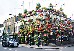 © London News Pictures. 26/07/2013 . London, UK.  The Churchill Arms on Kensington Church road, West London, covered in colourful bloom from top to bottom on a summers day. Gerry, who has been the landlord of the CHurchill Arms for 30 years, spends 2 weeks every year planting the flowers which are watered twice a day.  Photo credit : Ben Cawthra/LNP