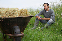 Man sitting beside wheelbarrow with hay in field