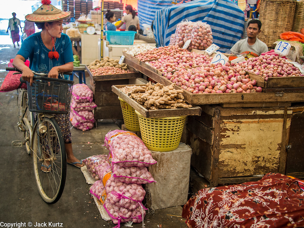 07 MARCH 2014 - MAE SOT, TAK, THAILAND:  A Burmese woman shopping in the market in Mae Sot talks to a man selling onions and garlic.    PHOTO BY JACK KURTZ