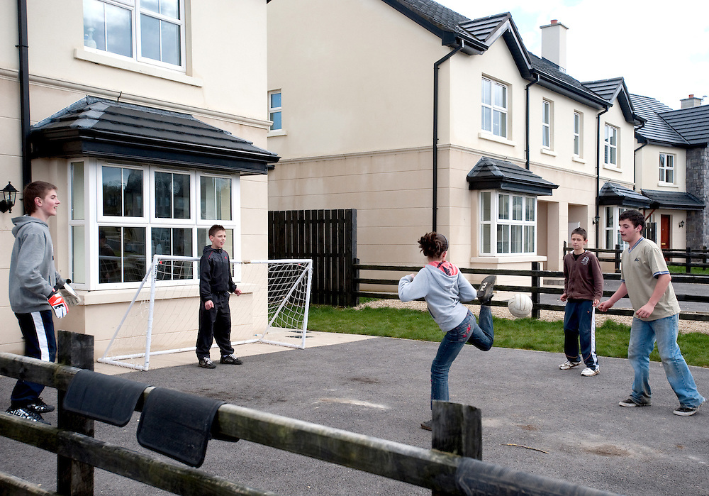 Aisling Maguire and her friends play football in the front garden of an empty house in Woodford Green, Newtowngore, Co. Leitrim.  Of 23 houses in the development, only 7 are occupied. The Semi detatched houses in the development were priced at EUR240,000 in 2006 and can now be bought for EUR130,000.