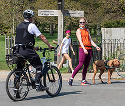© Licensed to London News Pictures. 11/04/2020. London, UK. A Police cyclists patrolling Richmond Park question a a dog walker during the coronavirus disease pandemic. Londoners have been told to stay at home and only leave homes to exercise or when absolutely essential in an attempt to fight the spread of COVID-19 as temperatures for the Easter Bank holiday weekend are expected to reach 26c. Photo credit: Alex Lentati/LNP