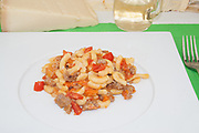 gramigna handmade pasta on white dish close-up from above with fork and parmesan with white wine on blured background,  italian traditional food of Modena