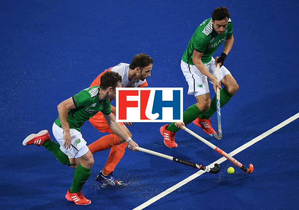 Ireland's John Jackson, Chris Cargo, and Netherland's Rogier Hofman stretch for the ball  during the men's field hockey Netherlands vs Ireland match of the Rio 2016 Olympics Games at the Olympic Hockey Centre in Rio de Janeiro on August, 7 2016. / AFP / MANAN VATSYAYANA        (Photo credit should read MANAN VATSYAYANA/AFP/Getty Images)