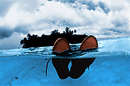 Man floating in ocean with shoes on on.
