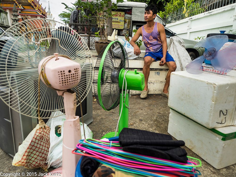 05 OCTOBER 2015 - BANGKOK, THAILAND: A man being evicted from the Wat Kalayanamit neighborhood with his belongings waits for a tuk-tuk (three wheeled taxi) to come for him. Fifty-four homes around Wat Kalayanamit, a historic Buddhist temple on the Chao Phraya River in the Thonburi section of Bangkok, are being razed and the residents evicted to make way for new development at the temple. The abbot of the temple said he was evicting the residents, who have lived on the temple grounds for generations, because their homes are unsafe and because he wants to improve the temple grounds. The evictions are a part of a Bangkok trend, especially along the Chao Phraya River and BTS light rail lines. Low income people are being evicted from their long time homes to make way for urban renewal.        PHOTO BY JACK KURTZ