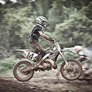 Panning shot shows a rider standing on the motorcycle and executing a single jump in foreground with another biker racing in the background on an extremely muddy motocross track in Belmopan, Belize.
