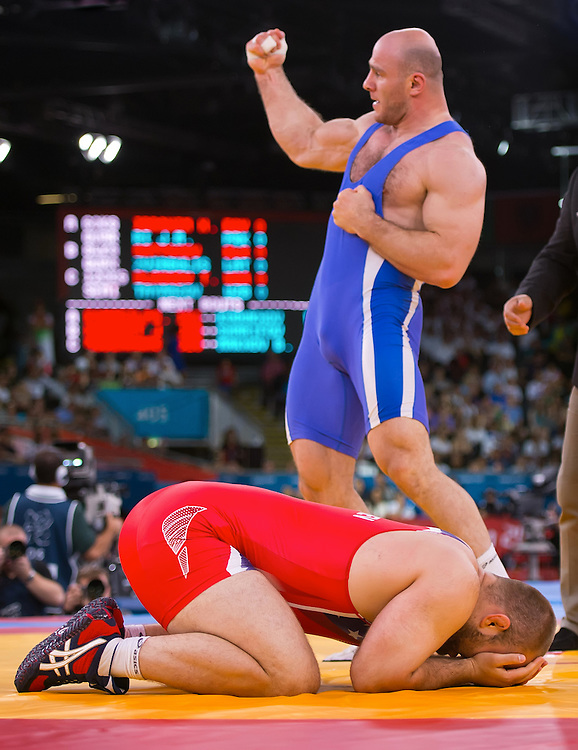 Tervel Dlagnev of the United States, foreground bottom in red, reacted to his loss in the men's freestyle 120kg semifinal match against Artur Taymazov of Uzbekistan, standing center, at the ExCeL centre during the 2012 Summer Olympic Games in London, England, Saturday, August 11, 2012. (David Eulitt/Kansas City Star/MCT)