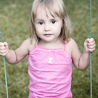 Young female child with fair hair sitting on swing looking at camera wearing pink top