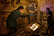 Researcher studing mummies in Sicily's crypts.