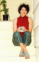 A 30ish woman sitting on her back steps sipping from a coffee mug.
