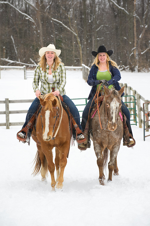 Two horse women friends out horseback riding in scenic winter snow, young adult country girl companions, western style clothing and cowboy hats,  rural Pennsylvania, PA, USA.