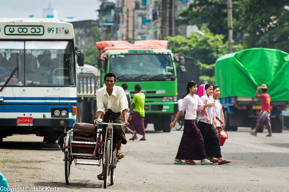 13 JUNE 2013 - YANGON, MYANMAR: A pedicab in traffic in Yangon. Yangon, formerly Rangoon, is Myanmar's commercial capital and used to be the national capital. The city is on the Irrawaddy River and has a vibrant riverfront.    PHOTO BY JACK KURTZ
