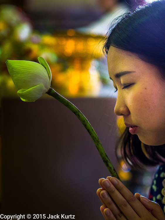 "04 MARCH 2015 - BANGKOK, THAILAND: A woman prays in the ""wiharn"" or prayer hall at Wat Benchamabophit on Makha Bucha Day. Makha Bucha Day is an important Buddhist holy day and public holiday in Thailand, Cambodia, Laos, and Myanmar. Many people go to temples to perform merit-making activities on Makha Bucha Day. Wat Benchamabophit is one of the most popular Buddhist temples in Bangkok.    PHOTO BY JACK KURTZ"