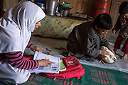 (Alison Griffin to fill in names) (girl's name) studies as her brothers play with a surviving livestock inside their house on the floor of the shelter built next to their collapsed home in Abikarpora village on the Dal Lake, Srinagar, Jammu and Kashmir, India, on 25th March 2015. Since the flood, she has been widowed, and is left with four young children and no home. Her family now lives in a temporary shelter built using the emergency shelter kit, and continues their recovery with the help of relief kits such as education kit, food basket, hygiene kit and non-food items from Save the Children. Photo by Suzanne Lee for Save the Children
