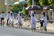 School girls dressed in Ao Dais on bicycles.