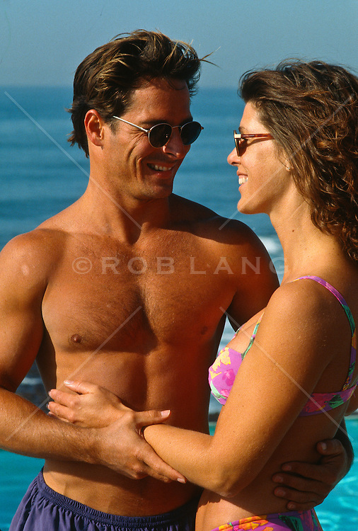 Good looking couple embracing and smiling while wearing swimsuits and sunglasses at the ocean in Mexico