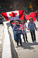 A man walks towards Downtown over Burrard Bridge, cheering and displaying a Canadian flag to vehicles driving in the other direction. Pictured with a group of children also involved in the celebrations.<br /> <br /> Tens of thousands of people in Vancouver took to the streets on Sunday 28th February 2010 to celebrate Canada's 3-2 overtime win over the United States for the gold medal in men's Olympic hockey...Traffic came to a halt in and around the downtown of the host city for the Winter Games following the dramatic finish to the match, which featured Sidney Crosby scoring to secure the victory on the final day of Olympic competition.