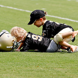 Aug 3, 2013; Metairie, LA, USA; New Orleans Saints quarterback Drew Brees (not pictured) son Baylen Brees (right) tackles his younger brother Bowen Brees as the kids played on the field following a scrimmage at the team training facility. Mandatory Credit: Derick E. Hingle-USA TODAY Sports